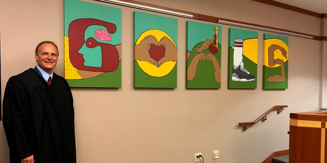 <p>Bay View High School students designed and painted the colorful works that hang behind Judge Dedinsky's bench.</p>